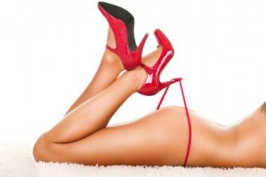 Woman's legs in heels playing with panties
