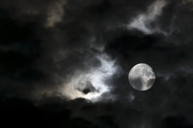 Vortex of eerie white clouds and full moon
