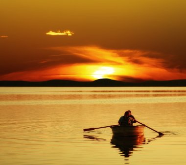 Couple rowing boat at sunset