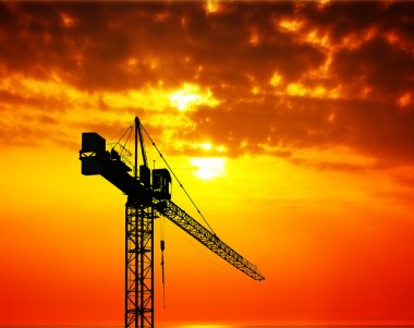 Industrial construction crane at sunset
