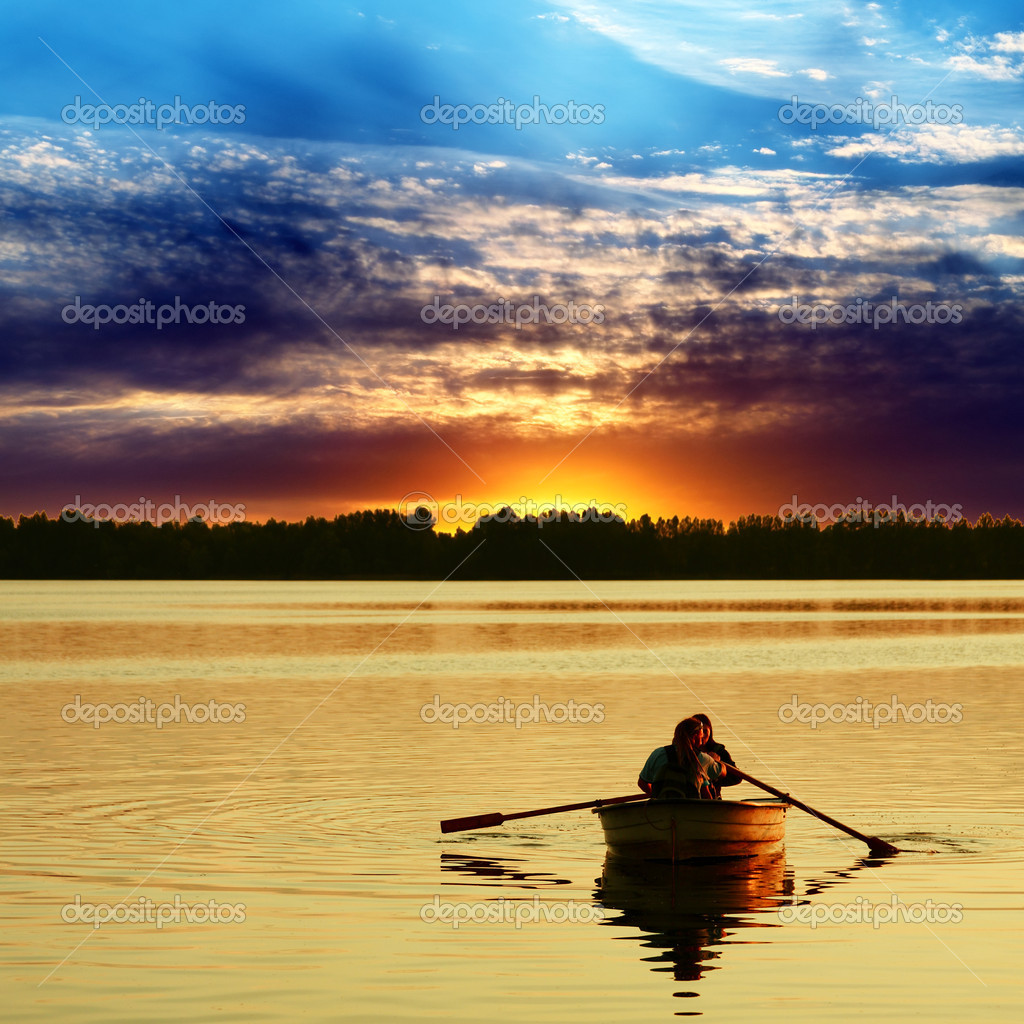 Couple in boat against a beautiful sunset