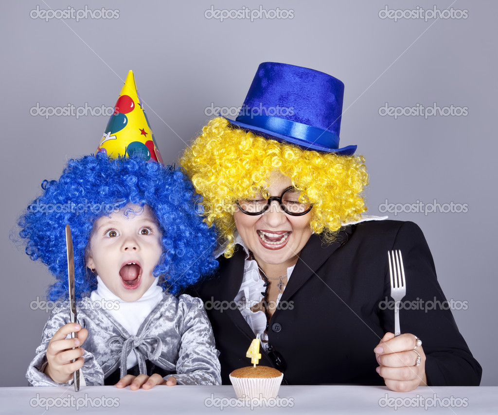 Mother and child in funny wigs and cake at birthday. Studio shot