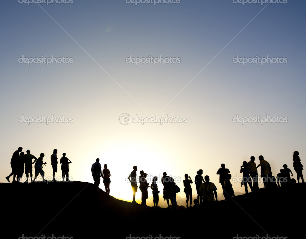 Group of silhouetted against the sun on top of a mountain
