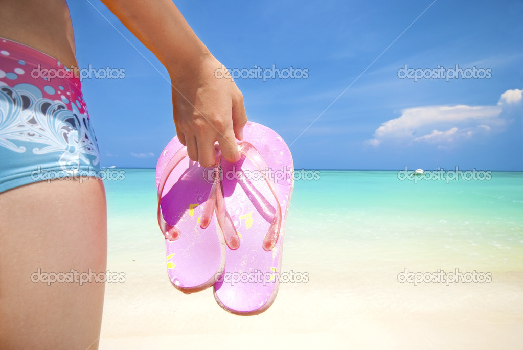Asian girl on a beach holding slipper