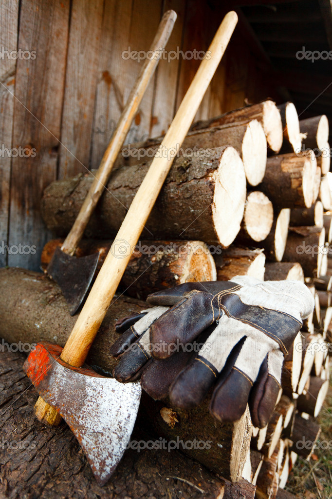 Axe, protective gloves and stack of logs