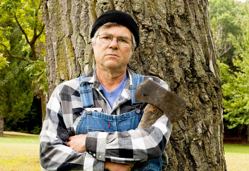 Man holding an axe leaning against a tree