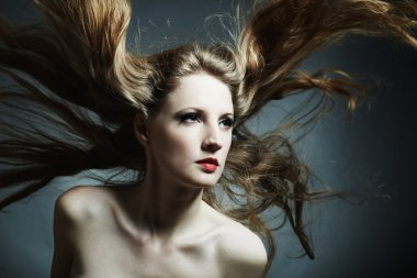 Fashion portrait of the young sexy woman with flying hair