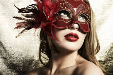 Beautiful young woman in a red mysterious venetian mask on a gold backgroun