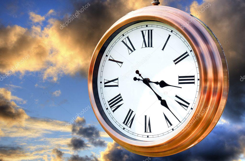 Copper clock on sunset sky