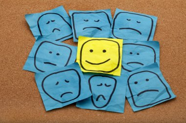 Positive attitude or optimism concept - happy smiley face on yellow sticky note surrounded by sad unhappy blue faces stock vector