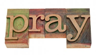 Pray word in vintage wooden letterpress printing blocks, stained by color inks, isolated on white stock vector