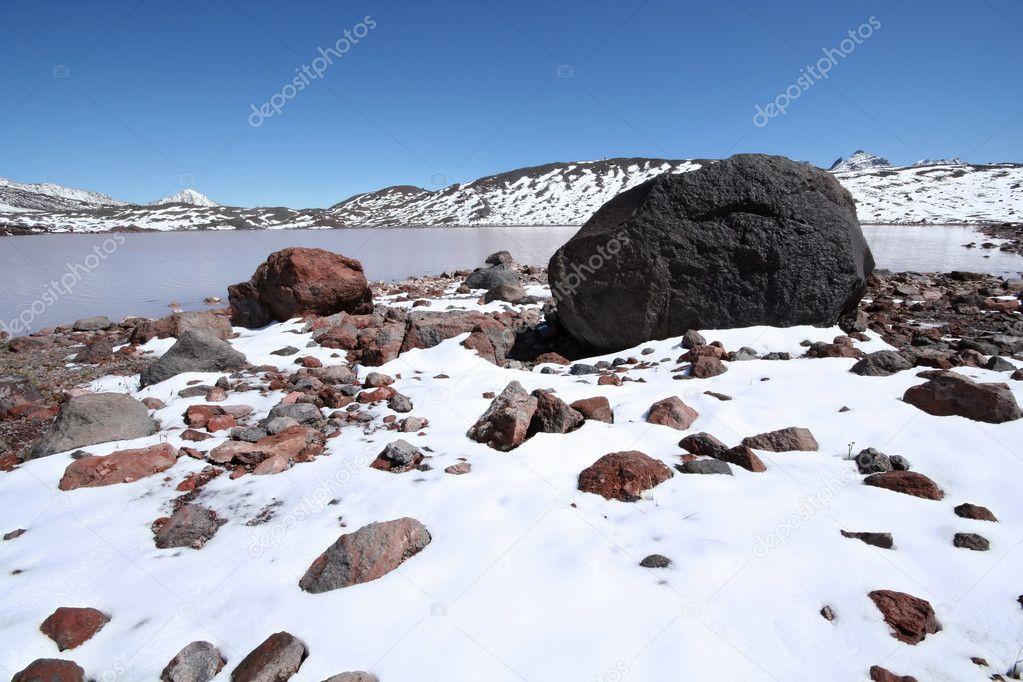Stones, rocks, snow and mountain lake, Caucasus.