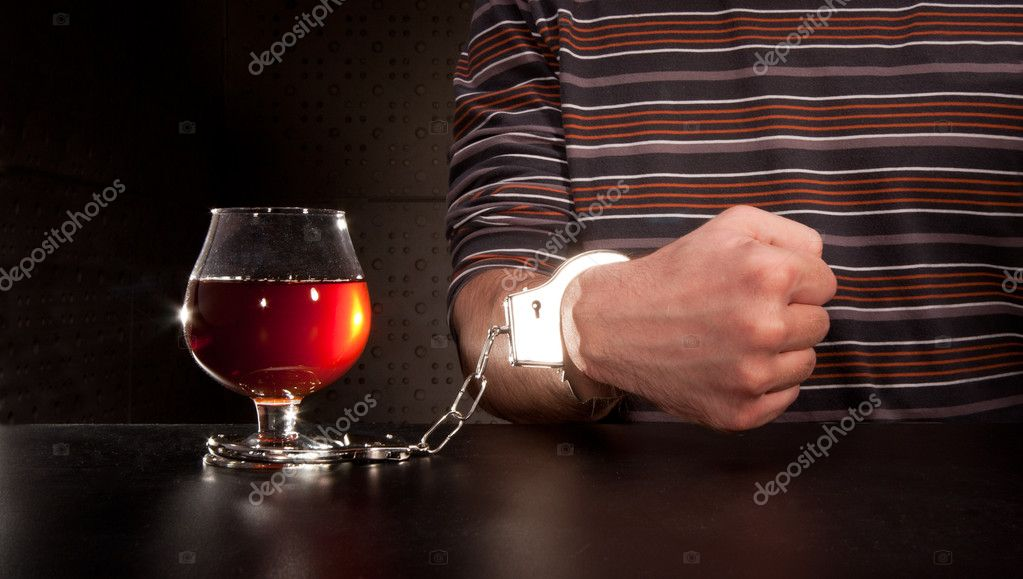 Hand locked to glass of alcohol