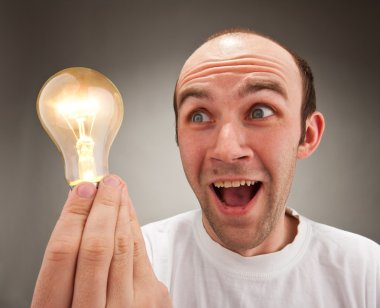 Surprised man holding lighting bulb