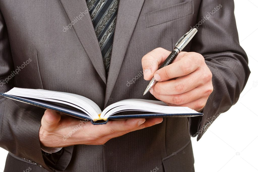 Businessman writing in business diary
