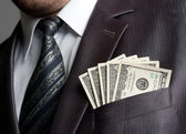 Uomo daffari con i soldi nella tasca del vestito