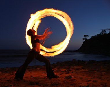 Firedancer along the beach at dusk.