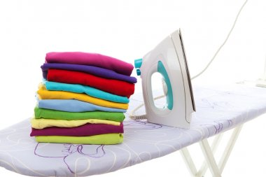 Pile of laundry and iron on ironing board