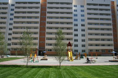 New apartment block with playground for kids, green grass.
