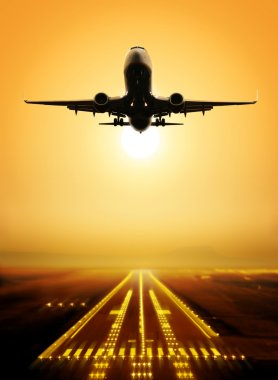 Passenger plane fly up over take-off runway from airport at sunset stock vector