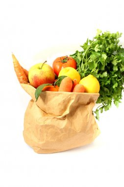 Fresh raw vegetables and fruits in a paper bag isolated on a white backgrou