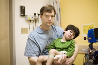 Worried father and child is doctor's office