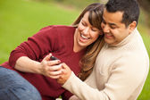 Fotografie Attractive Mixed Race Couple Enjoying Their Camera Phone