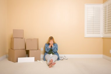 Upset Woman on Floor Next to Boxes and Blank Sign