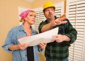 Auftragnehmer in Bauarbeiterhelm Pläne mit Frau besprechen