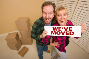 Goofy Couple Holding We've Moved Sign Surrounded by Boxes