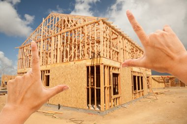 Female Hands Framing Home Frame on Construction Site