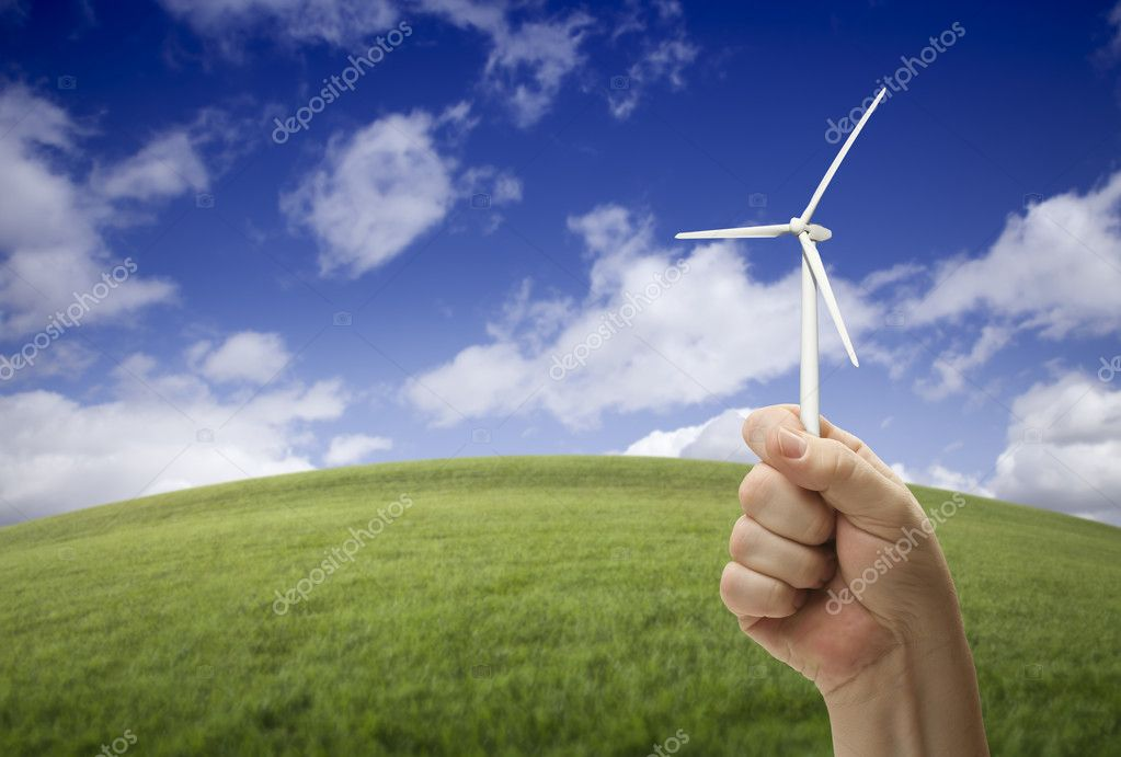 Male Fist Holding Wind Turbine Outside with Grass Field