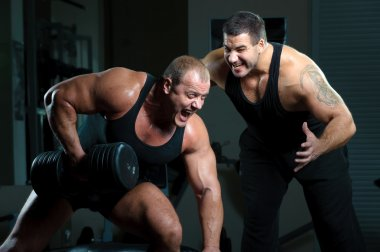 Two bodybuilders training in gym