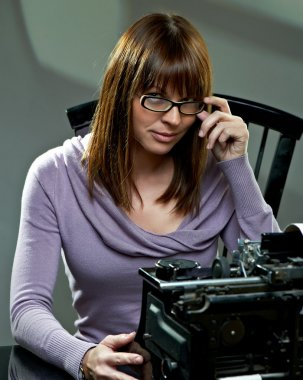 Beautiful young woman in glasses at a typewriter