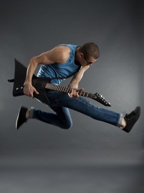 Rock star jumping with guitar