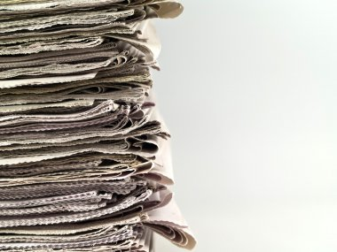 Old newspapers stacked from the top to bottom of the frame isolated on whit