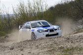 Fotografie White racing rally car on gravel road