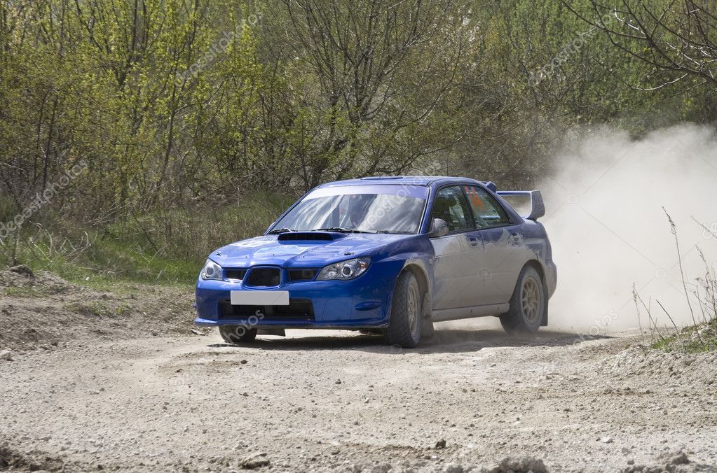 Blue racing rally car on gravel road