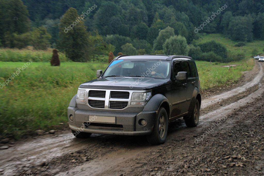 Black car on dirt road