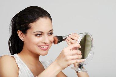 Hispanic woman putting on her makeup
