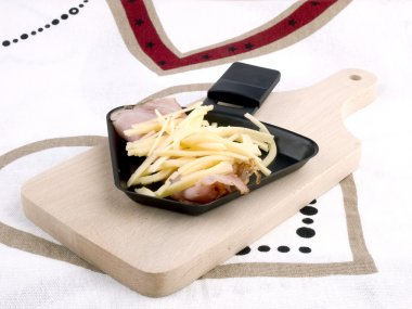 Raclette pan with cheese and ham - party food