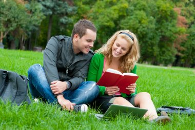 Two students reding the book on the grass