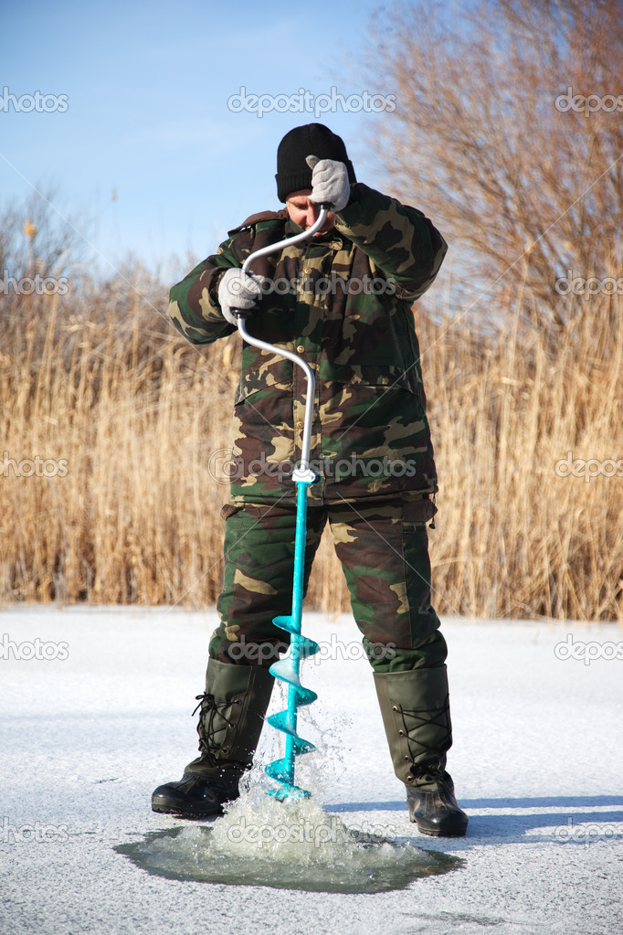 Fisherman drill on winter lake