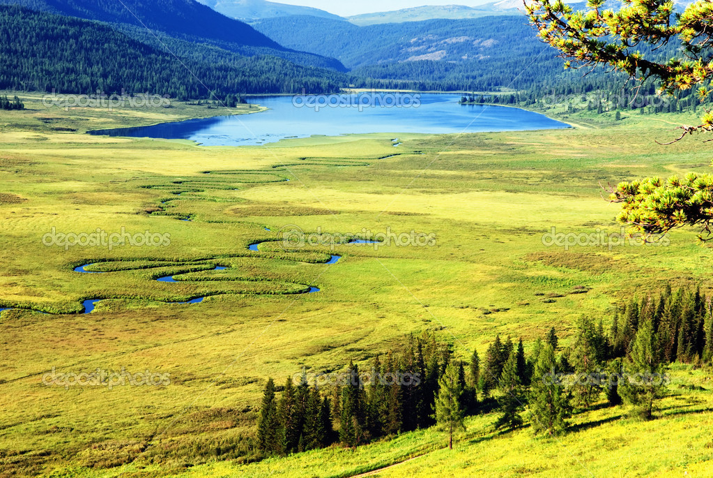 Curved river on meadow and mountain lake