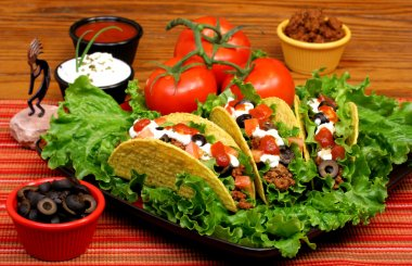 Tacos in a bed of greens with tomatoes and garnishes to the side.