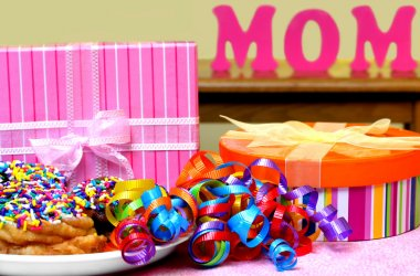 Decorated doughnuts, presents, and curled ribbons ready for Mom. The word MOM in the background. stock vector