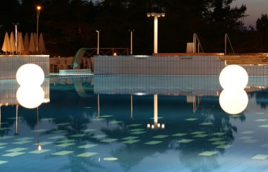 Large Glowing light in the form of a ball in the water at night in the pool