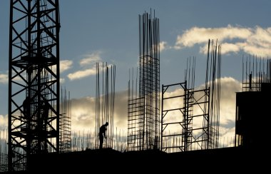 Silhouettes of construction workers, construction equipment and elements of