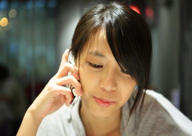 Woman talking on the phone in restaurant