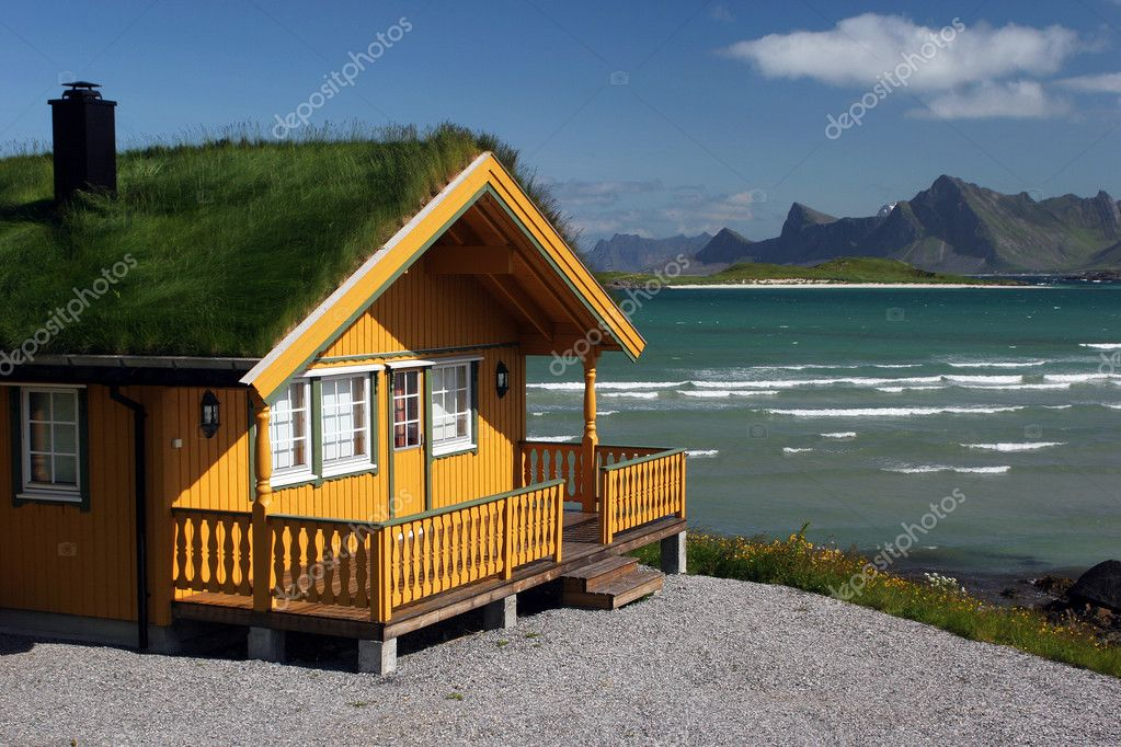 Yellow wooden house with grass roof